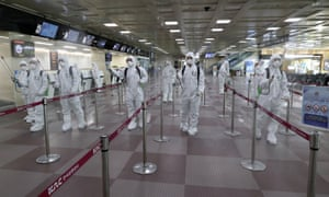 South Korean soldiers wearing protective gear spray disinfectant to help prevent the spread of the coronavirus at the Daegu international airport.