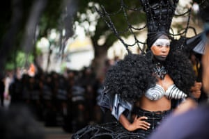 A performer in elaborate headdress and conical bra in a traditional street procession in Havana