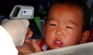 A worker checks a child's temperature during the Sars outbreak in 2003.