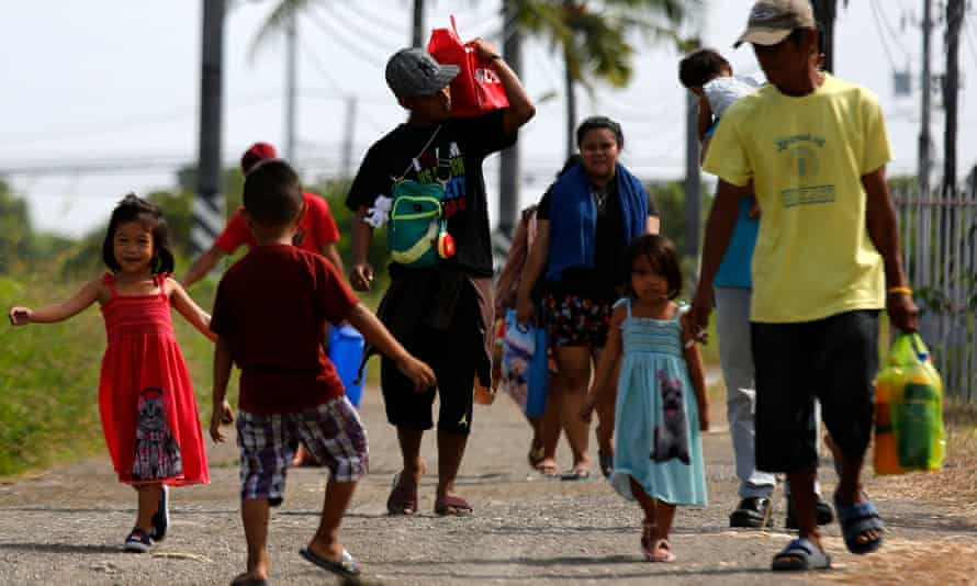 Filipino villagers evacuate a coastal village in Cavite province on Christmas Day as authorities evacuated thousands in preparation for typhoon Nock-ten.