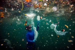 A female diver surrounded by plastic waste under water including face masks