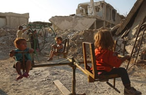 Children play on a roundabout in a street destroyed during the war in the rebel-held town of Douma as Muslims celebrate the holiday of Eid al-Adha.