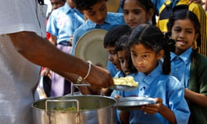 A girl looks at food served to her for free at a government-run school in Bangalore, India