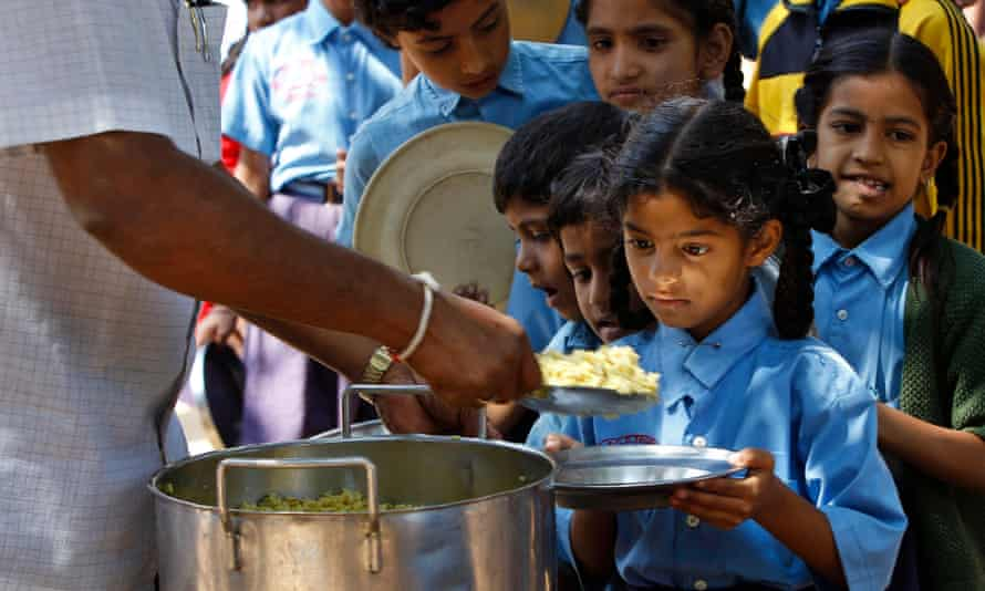 Schoolchildren queue for food at a school in Bangalore. Studies have shown that girls in India receive less education and poorer nutrition than boys.