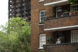 In the shadow of Grenfell… A woman stands on the balcony of her home, close to Grenfell Tower, two days after the block was engulfed in flames.