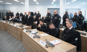 The accused sit in a courtroom in Dresden, eastern Germany.