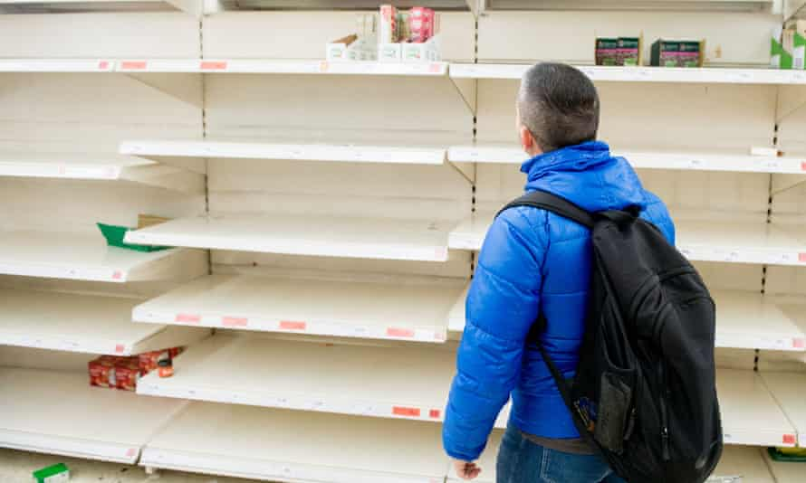 A shopper in front of empty rice and tinned goods shelves at a Sainsbury's.