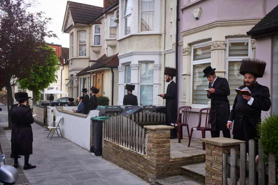 Haredi Jewish men pray in their front gardens for daily morning services. All synagogues are closed during lockdown, so members of the community are instead forming minyans (quorum of 10 men) in their front and back gardens. Stamford Hill, London,