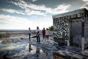 The Krishalingam family, Tamils with refugees status, stand on the rooftop of an abandoned mansion in Ronave, Nauru. Local refugees have painted script over rooftop. Nauru 2018.