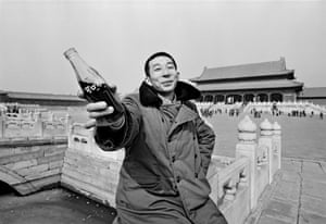 A young man proffers a bottle of Coca-Cola in Beijing