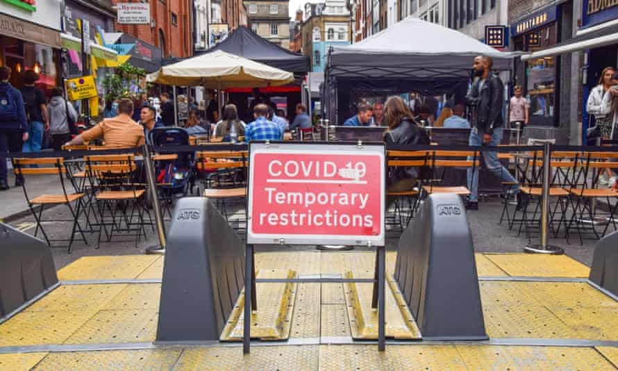Covid restrictions sign seen by outdoor restaurant tables in Old Compton Street, Soho, London.