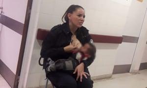 Police officer Celeste Ayala comforts a baby