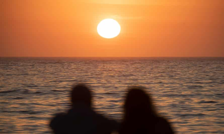 silhouettes of two people looking at the sun rise over the ocean's horizon