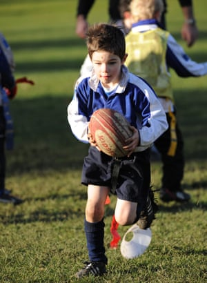 Young boy with muddy knees running with a rugby ball during a training session with other players in the background