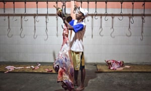 A worker weighing beef in an abattoir in Indonesia