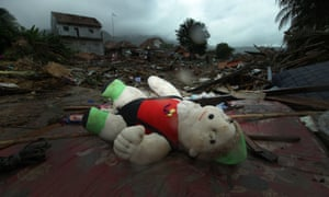 A doll lost to its owner lies in the ruins of a home.