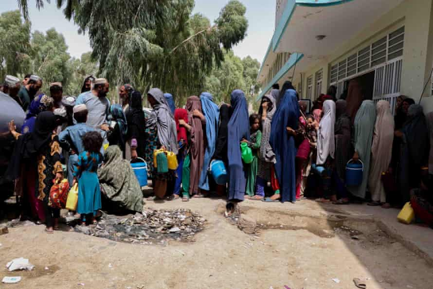 Families wait for relief at temporary shelters in Kandahar as the Taliban continued their surge in Afghanistan