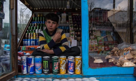 Mustafa, 13, sits in his cousin's shop, selling dozens of different kinds of energy drinks.