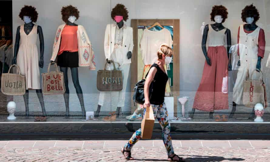 A woman in a mask walks by a store window of mannequins wearing masks