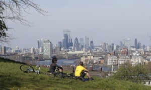 Cyclists sit on the upper slopes of Greenwich Park overlooking the London skyline.