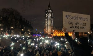 People gathered in Parliament Square, London, use mobile phones as torches and hold placards, the day after clashes between police and crowds who gathered on Clapham Common on Saturday night to remember Sarah Everard.