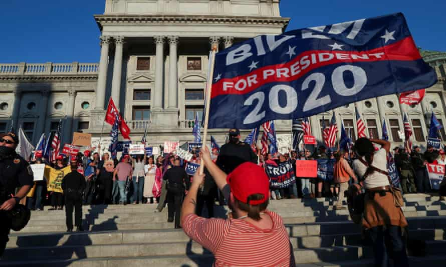 Supporters of Donald Trump rally as a supporter of Joe Biden celebrates outside the Pennsylvania state capitol building in Harrisburg on 7 November.