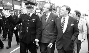 Sir David McNee, front right, and William Whitelaw, the home secretary, centre, are taken on a tour of riot-torn Brixton, south London.