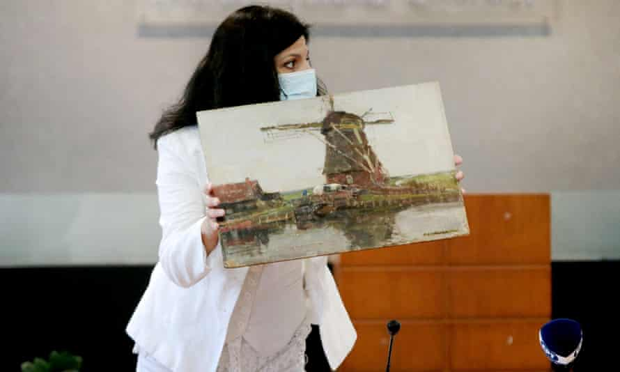 A Greek police officer presents the stolen Mondrian painting at a press conference in Athens