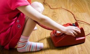 A young girls answers a vintage red telephone