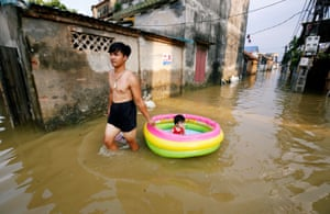 Hanoi, Vietnam: A man pulls his daughter in a paddling pool in a flooded village after heavy rainfall caused by tropical storm Son Tinh