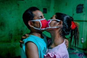 Toma and Tuktuki kiss through masks during the Covid lockdown in Dhaka, Bangladesh, 2020