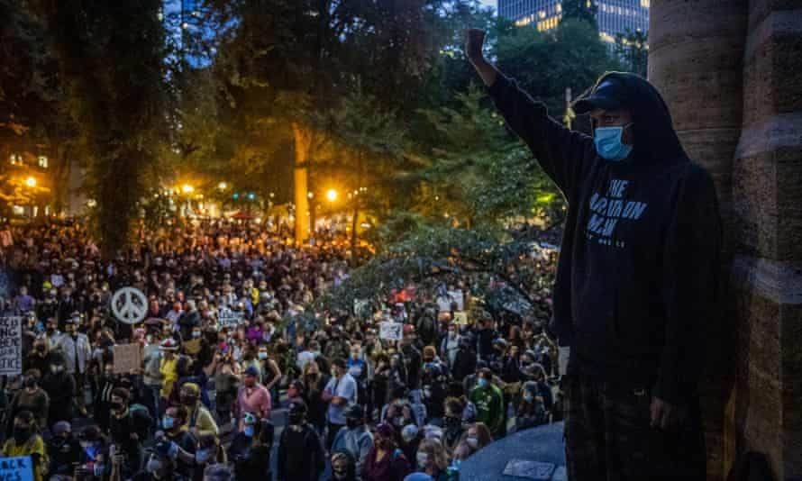 Matthew Pine, 20, of Portland, raises his fist as protesters listen to speakers.