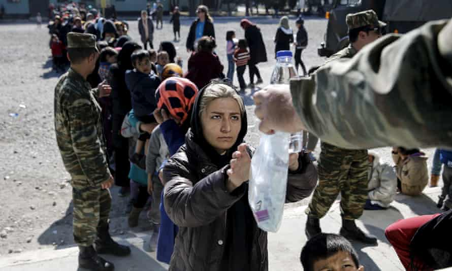 A woman receives food and water at a relocation camp in Schisto, a suburb of Athens.