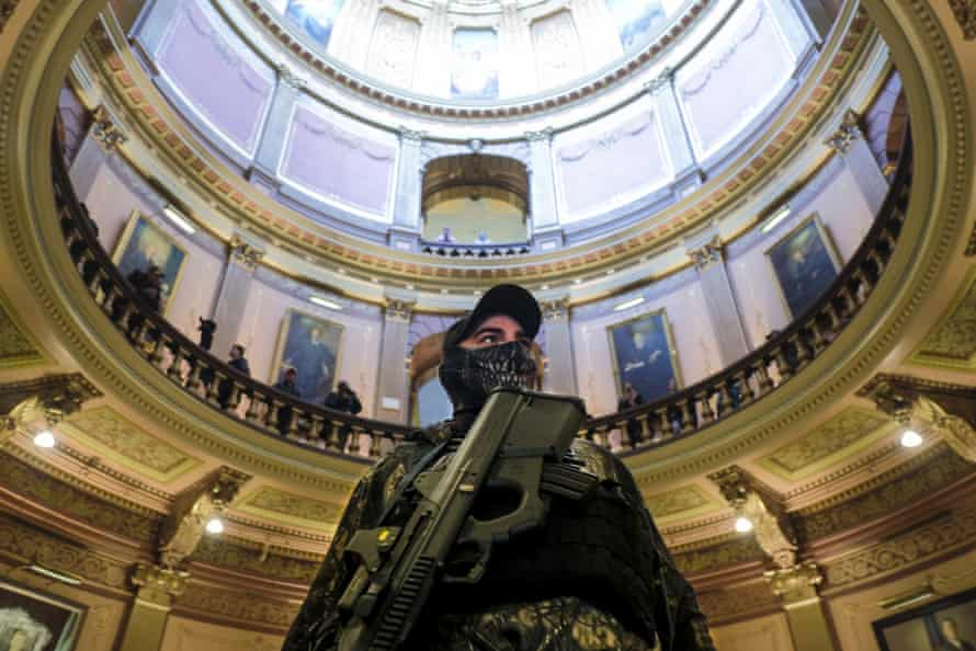 An armed protester wearing a mask stands at the Michigan capitol building in Lansing, Michigan, on 30 April.
