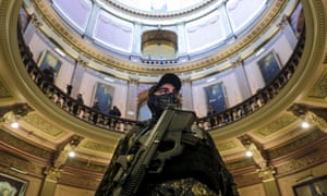 An armed extremist stands in the Michigan Capitol building in Lansing, Michigan, in April 2020 as part of a protest against Governor Gretchen Whitmer's coronavirus stay-at-home order. Subsequently several people were charged with a plot to kidnap Whitmer.