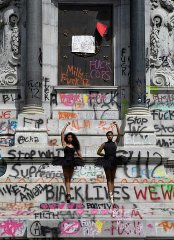 Ballerinas Kennedy George, 14, and Ava Holloway, 14, pose in front of a monument of Confederate general Robert E. Lee after Virginia Governor Ralph Northam ordered its removal.