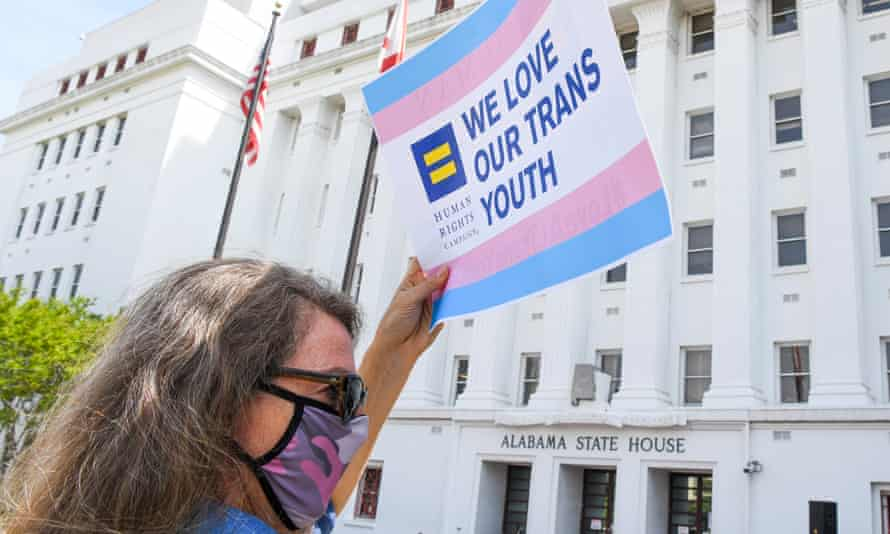 A sign reading 'We love our trans youth' is seen during a rally outside the Alabama state house in Montgomery on 30 March.