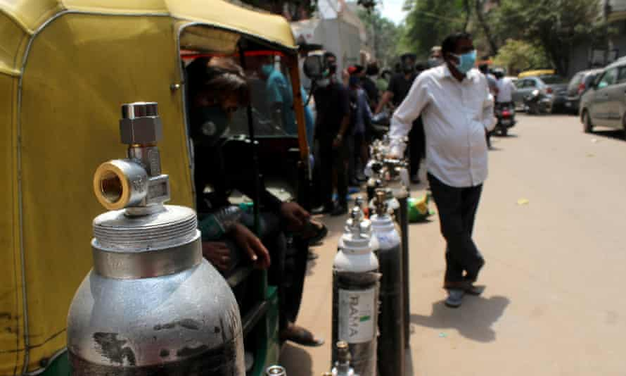 People stand in a queue with their oxygen cylinders outside a shop to get them refilled in Delhi.