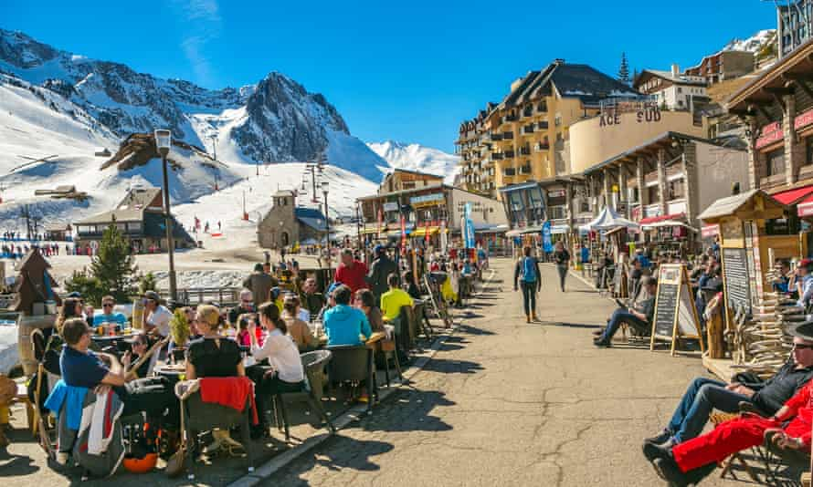 Diners at outdoor restaurants, while other people sit an relax on benches on a sunny winter day at the Grand Tourmalet ski area, La Mongie, French Pyrenees.