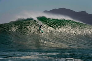 Cape Town, South Africa. A surfer catches a wave at Sunset, a surfing spot between Hout Bay and Kommetjie that produces some of the country's biggest waves. This relies on several factors, including wind, swell size, wave period and direction, which often follow storms to produce huge waves on this reef