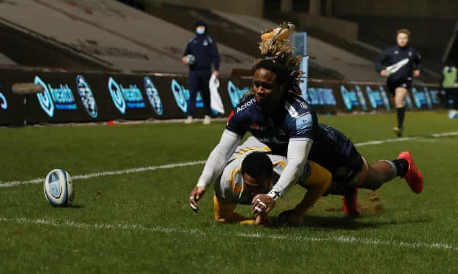 Sale's Marland Yarde falls on Wasps' Zach Kibridge as they race for the loose ball near the try-line in the Premiership match at the AJ Bell Stadium.