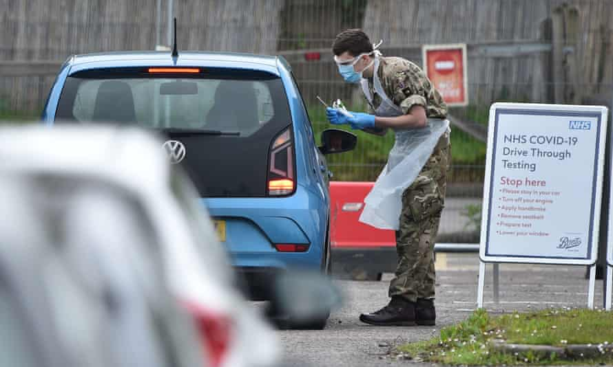 A member of the armed forces tests an NHS worker for the coronavirus at a facility at the Chessington World of Adventures on 18 April.