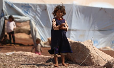 A displaced Syrian girl stands outside her tent in a camp in Kafr Lusin.