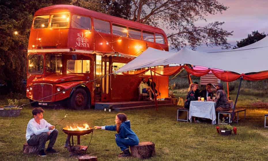 At dusk, double decker bus in field at Nesta camping, Somerset, UK