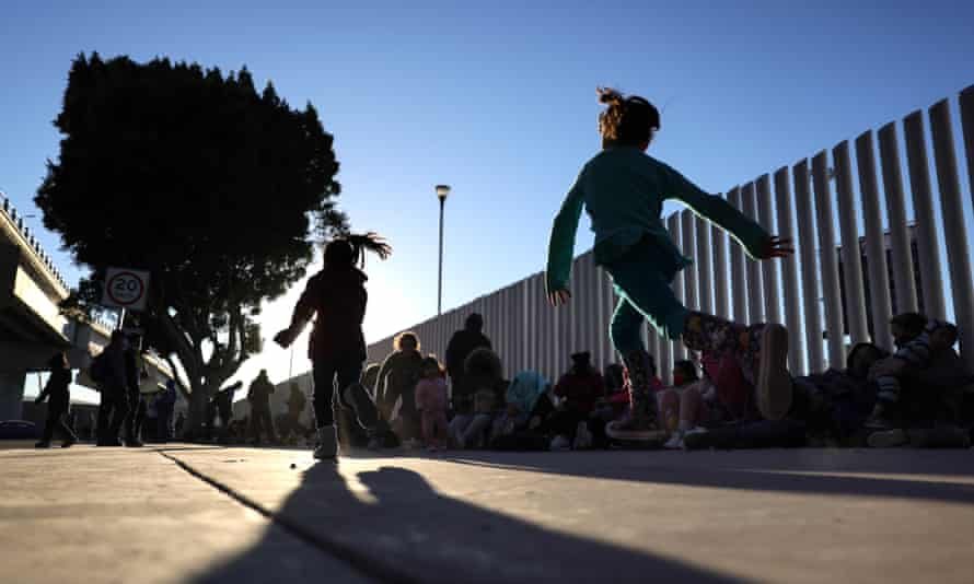 Children play near a line of people seeking asylum in the United States in Tijuana, Mexico.