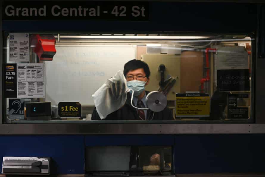 A transit worker wears a mask as he cleans the window of a booth in the Grand Central subway station.