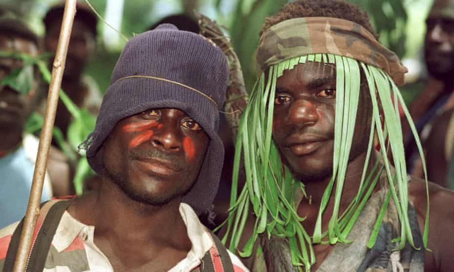 Guerillas of the Bougainville Revolutionary Army (BRA), some still wearing camouflage, watch the signing ceremony of the Bougainville Ceasefire Agreement at Arawa on Bougainville 30 April 1998.