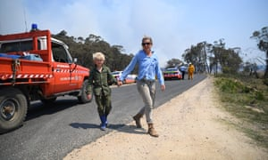 Katie Rossington and her son Gus wait at a roadblock to get to their property as smoke from a large bushfire is seen outside Wytaliba, near Glen Innes, on Sunday