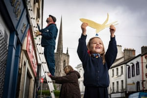 Enniskillen, UK. Thea Johnston of Enniskillen integrated primary school helps the artists Simon Carman and Helen Sharp as they begin the installation of 150 swallows in gold leaf in the Northern Irish town, to mark the launch of a new literary tourism initiative