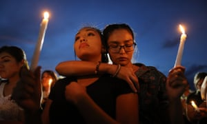 People attend a candlelight vigil at a makeshift memorial honoring victims of the El Paso shooting.